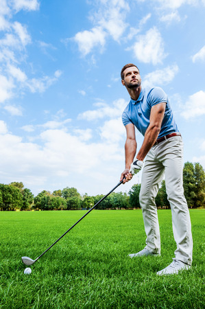 off course: Ready to strike. Low angle view of young man playing golf while standing on green Stock Photo