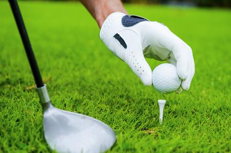 golf glove: Preparing for strike. Close-up of golfer setting a ball to strike
