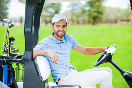 On my way to the next hole. Side view of young happy male golfer driving a golf cart and looking at camera photo