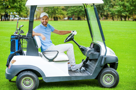 Man driving golf cart. Side view of handsome young man driving a golf cart and looking at camera photo