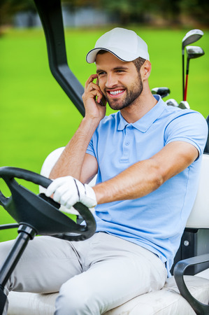 I will meet you on green! Handsome young smiling man driving a golf cart and talking on the mobile phone  photo