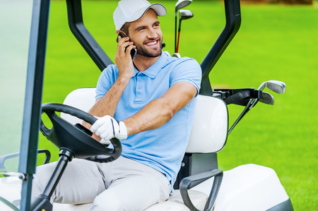 Great day to play golf! Handsome young smiling man driving a golf cart and talking on the mobile phone  photo