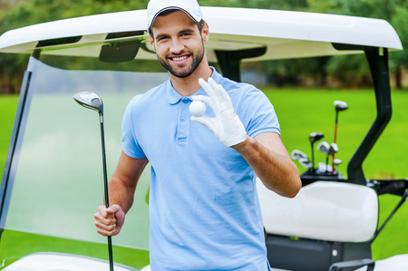 Only the best golf equipment! Handsome young smiling man holding golf ball and driver while standing near the golf cart and on golf course photo