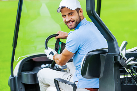 only man: On his way to the next hole. Rear view of young happy male golfer driving a golf cart and looking over shoulder
