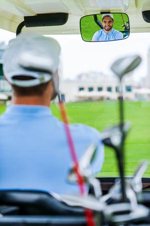 rear view mirror: En su camino hacia el siguiente hoyo. Golfista masculino feliz joven que conduce un carrito de golf y mirando el espejo retrovisor