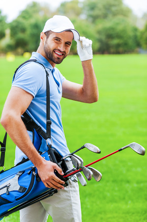 golf bag: I love golfing! Rear view of young happy golfer carrying golf bag with drivers and looking over shoulder while standing on golf course Stock Photo