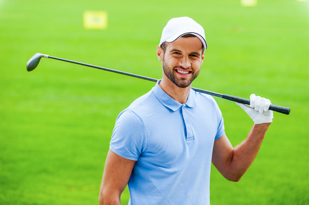 professional sport: Confident golfer. Young happy golfer carrying driver on shoulder and smiling while standing on golf course
