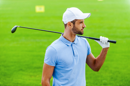 polo sport: Thinking about next shot. Confident male golfer carrying driver on shoulder and looking away while standing on golf course