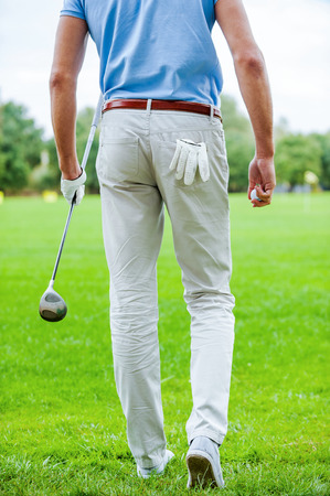 golf glove: Ready to play golf. Rear view of male golfer walking away while holding golf ball and driver  Stock Photo