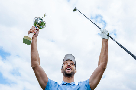 sports trophy: Happy winner. Low angle view of young happy golfer holding driver and trophy while raising his arms with blue sky as background
