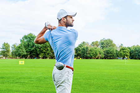 competition success: Great strike. Side view of confident golfer swinging his driver and looking away while standing on golf course