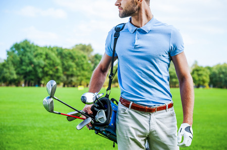 polo shirt: Golf is a style of living. Cropped image of male golfer carrying golf bag with drivers while walking by green grass