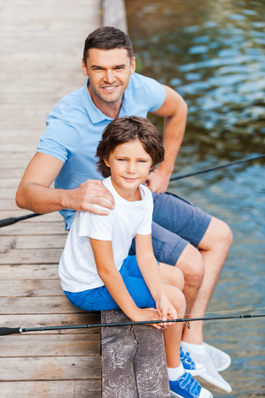 Spending great time together. Top view of father and son looking at camera and smiling while sitting at the quayside with fishing rods laying near them photo