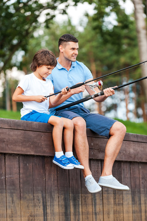 Fishing together. Cheerful father and son fishing while sitting on quayside photo