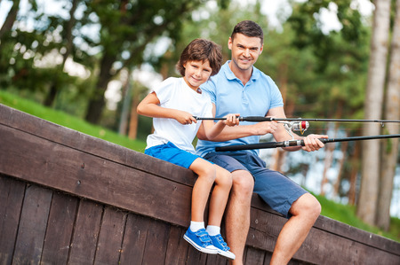 We love fishing together. Cheerful father and son fishing together and smiling while sitting on quayside photo