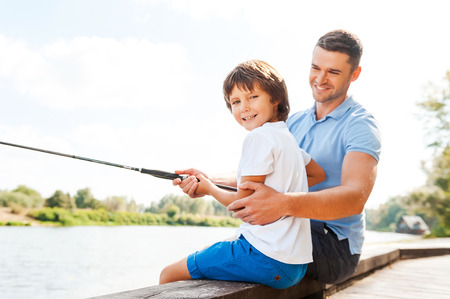 Fishing together is fun. Cheerful father and son fishing together while little boy looking at camera and smiling