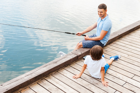 My father is the best in fishing. Top view of cheerful father and son fishing together while sitting at the riverbank Stock Photo