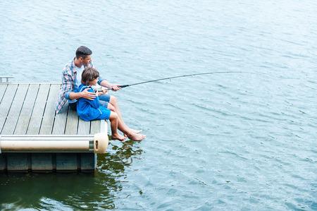 pescando: Padre e hijo de pesca. Vista superior de padre e hijo juntos de pesca en el muelle