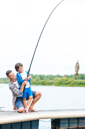 It is a big fish! Father and son stretching a fishing rod with fish on the hook  photo