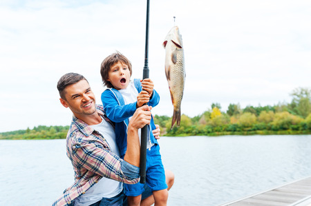 It is so big! Father and son stretching a fishing rod with fish on the hook while little boy looking excited and keeping mouth open Foto de archivo