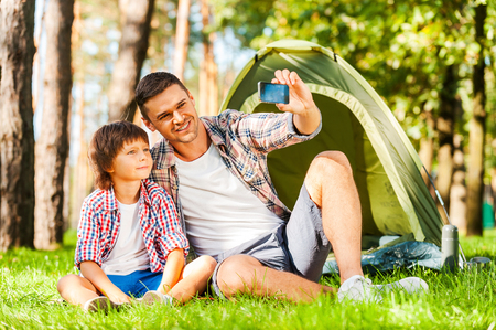 Capturing the bright moments. Cheerful father and son sitting near the tent while camping in the forest   photo