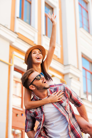 Spending great time together. Happy young man carrying his beautiful girlfriend on shoulders and smiling while walking by the street Stock Photo