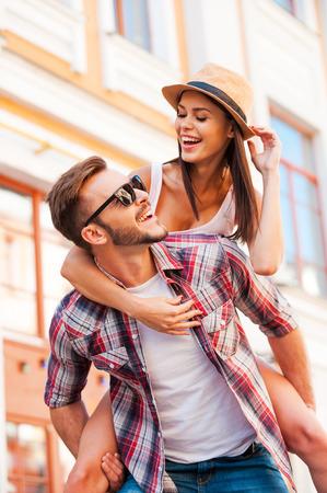 Plezier samen. Gelukkig jonge man met zijn mooie vriendin op de schouders en glimlachen tijdens het wandelen door de straat