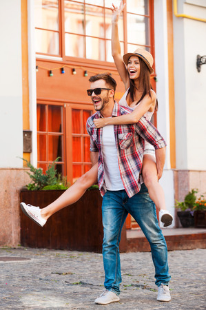 Young and carefree. Full length of happy young man carrying his beautiful girlfriend on shoulders and smiling while walking by the street