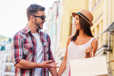 shopping scene: Enjoying their time together. Beautiful young loving couple walking by the street and talking to each other while beautiful woman carrying shopping bags and smiling