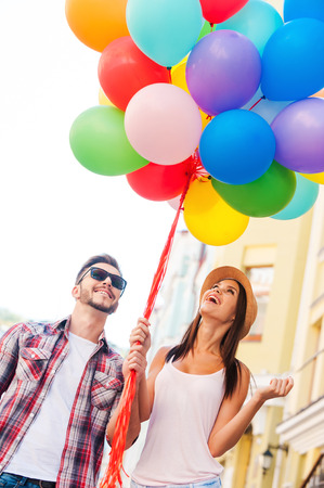 headwear: Living a colorful life. Beautiful young loving couple carrying multi colored balloons and smiling while standing outdoors