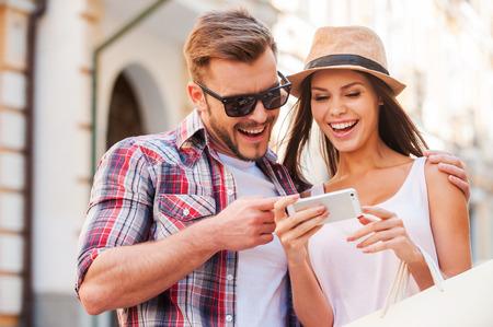 Gelukkig paar met slimme telefoon. Gelukkige jonge liefdevolle paar staande samen buitenshuis en kijken naar de mobiele telefoon samen