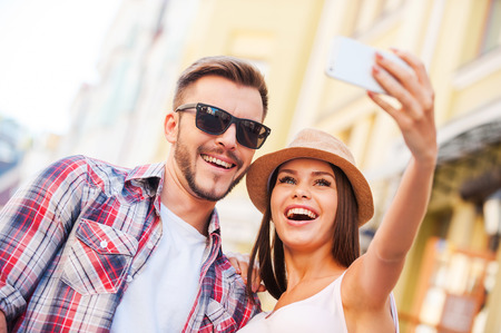 happy moment: Capturing a happy moment. Low angle view of happy young loving couple making selfie while standing outdoors together  Stock Photo