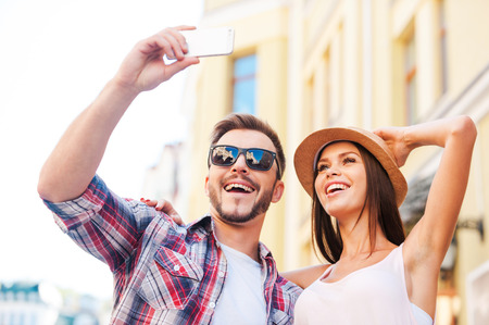 making love: We love making selfies. Low angle view of happy young loving couple making selfie while standing outdoors together  Stock Photo