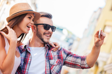 heterosexual couple: We are looking just great! Side view of happy young loving couple making selfie while standing outdoors together  Stock Photo