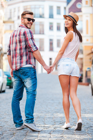 Enjoying their time together. Rear view of beautiful young loving couple walking by the street and looking over shoulder  Stock Photo