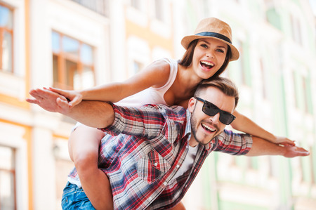 Happy loving couple. Happy young man piggybacking his girlfriend while keeping arms outstretched  Standard-Bild
