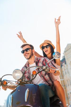 motorrad frau: Das Fahren mit Spaß. Schöne junge Paare Reiten Roller zusammen, während glückliche Frau Heben der Arme und lächelt