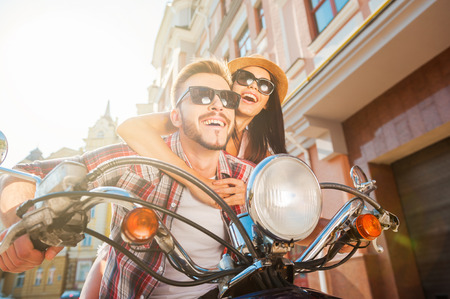 Fun ride. Beautiful young couple riding scooter together while happy woman bonding to her boyfriend and smiling