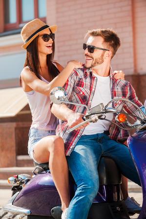 vespa piaggio: Godendo il loro tempo insieme. Bella coppia di giovani seduti sul motorino insieme mentre bell'uomo guardando sopra la spalla e sorridendo Archivio Fotografico