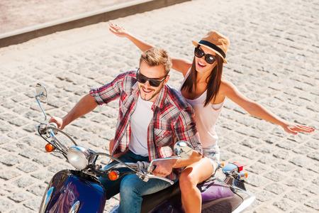 vespa piaggio: Avendo grande divertimento insieme. Vista dall'alto di bella giovane coppia giro in scooter insieme, mentre la donna felice tenendo le braccia aperte e sorridente Archivio Fotografico