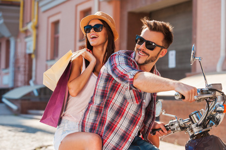 cool people: Young and carefree. Side view of beautiful young couple riding scooter together while happy woman carrying shopping bags and bonding Stock Photo