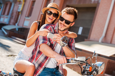 Look at this photo! Beautiful young couple sitting on scooter together while happy woman showing something at her mobile phone Stock Photo - 31968576