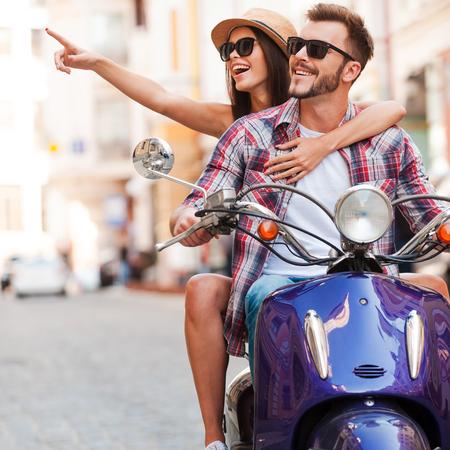 Kijk maar naar dat! Mooie jonge paar rijden scooter samen terwijl gelukkige vrouw die weg en glimlachen Stockfoto