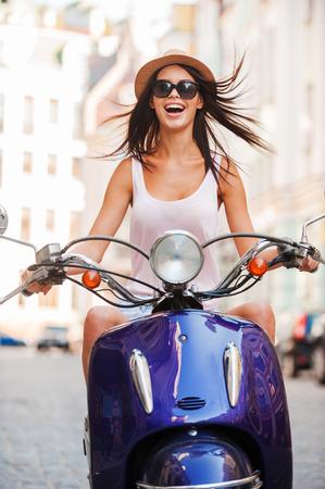 vespa piaggio: Beauty on scooter. Eccitato giovane e bella donna equitazione scooter lungo la strada e mantenere la bocca aperta