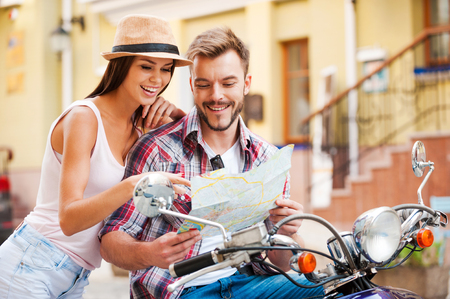 love life: Looking for place to go. Beautiful young loving couple sitting on scooter together and examining map while woman pointing it and smiling