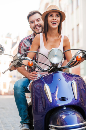 Riding scooter is such a fun! Beautiful young couple riding scooter along a street and smiling  Stock Photo