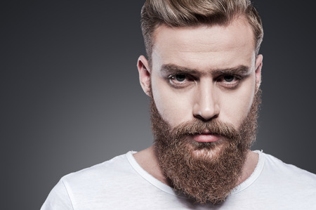 barber background: Confidence and masculinity. Portrait of handsome young bearded man looking at camera while standing against grey background