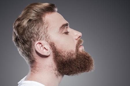 hombre con barba: Barbudo guapo. Vista lateral de guapos jóvenes barbudos hombre manteniendo los ojos cerrados mientras está de pie contra el fondo gris