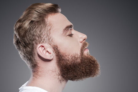 hipster: Bearded handsome. Side view of handsome young bearded man keeping eyes closed while standing against grey background