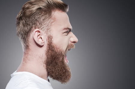 Unleashing his emotions. Side view of furious young bearded man shouting while standing against grey background 스톡 콘텐츠